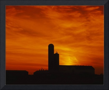 Silhouette of a barn and a silo at sunset