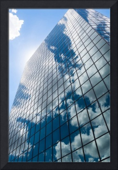 tall glass building with reflection of blue sky an