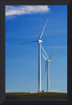 Pair of wind farm turbines in green grass