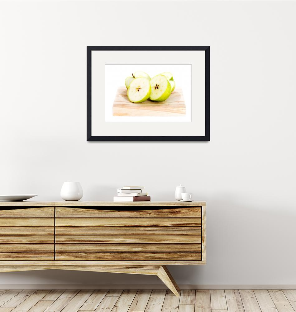 """Green apples divided into two half. On wooden back""  by Piotr_Marcinski"
